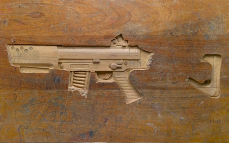 Gun Carved into a Wooden Desk